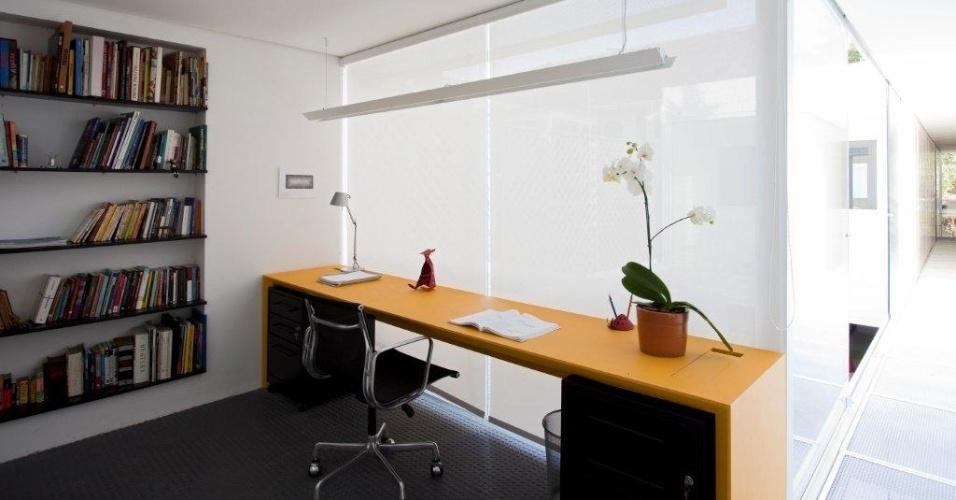 Aproveitando o hall criado pela escada, os arquitetos instalaram, no primeiro pavimento, um escritório simples e prático, com mesa de trabalho em linhas retas e duas cores: base preta e tampo amarelo, o único toque colorido da casa. Na parede, estante com prateleiras pretas guardam livros