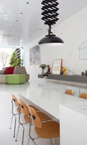 Inusitada, a cozinha virou o coração da casa. O rebaixo de 75 cm do térreo possibilitou sua instalação de modo original, ou seja, na parte frontal da casa. Destaque para a mesa de refeições que dá continuidade ao piso da sala de estar. A solução permitiu aumentar o pé-direito (ficou com 3,21 m) e a integração da sala com o jardim externo. A luminária tipo pendente pantográfico é da Fama Artigos Fotográficos