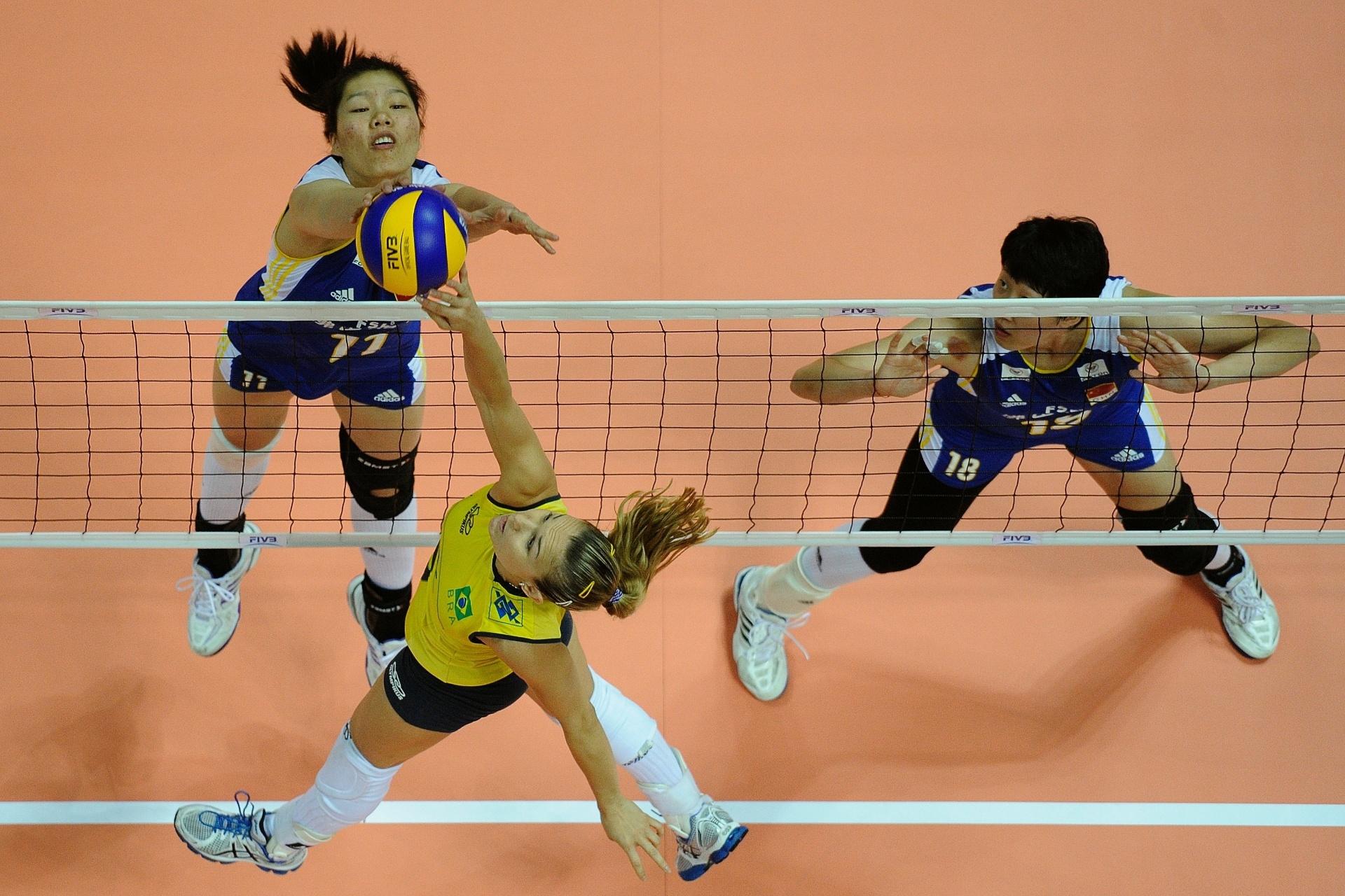 Levantadora Fernandinha disputa bola na rede contra rival chinesa