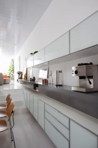 Na cozinha, a mesa de refeições dá continuidade ao piso da sala de estar. Os armários brancos com vidros leitosos desenhados pela arquiteta acomodam eletrodomésticos e utensílios. O projeto é assinado pelos arquitetos e proprietários Lourenço Gimenes (escritório FGMF) e Clara Reynaldo (escritório CR2)
