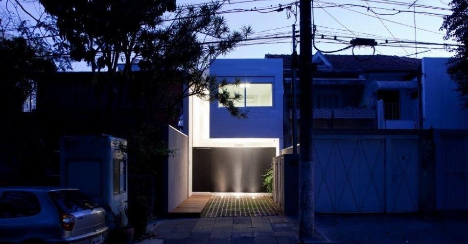Na visão noturna da casa, a iluminação intensa tanto no interior quanto na fachada é realçada por spots instalados no piso da garagem descoberta. A transparência dos vidros permite visualizar o painel de ladrilhos hidráulicos que reveste a parede e se prolonga por todos os pavimentos