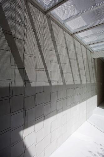 O reflexo da luz solar revela o desenho dos ladrilhos que formam o painel da parede e a trama da malha expandida empregada na passarela do primeiro pavimento. O projeto da residência é assinado pelos arquitetos e proprietários Lourenço Gimenes (escritório FGMF) e Clara Reynaldo (escritório CR2)