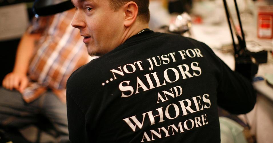 14.abr.2012 - Homem mostra sua camiseta em defesa das tatuagens, na qual lê-se, em inglês,