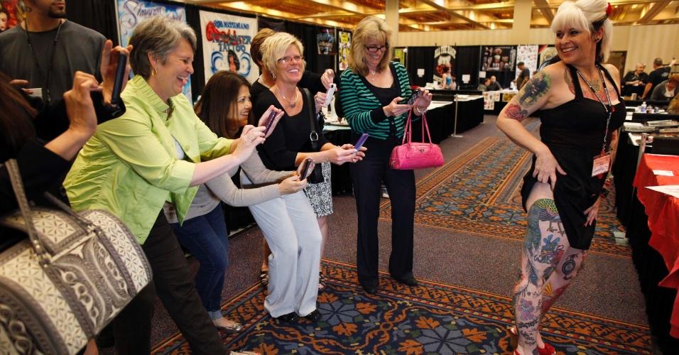 14.abr.2012 - Um grupo de mulheres que estava numa feira vizinha de roupas de cama acabou entrando numa convenção nacional de tatuagem, em Ohio (EUA), e aproveitou para tirar fotos