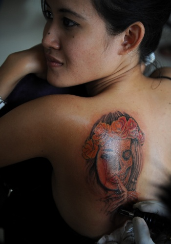 23.jun.2012 - Tatuador desenha nas costas de uma mulher durante competi&#231;&#227;o de tatuagem na ilha de Bali, na Indon&#233;sia