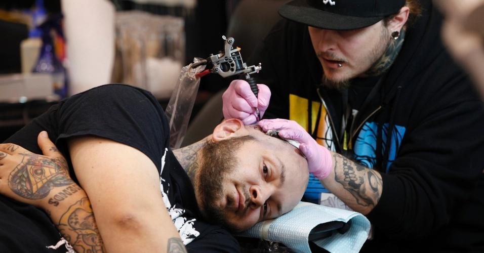 2.mar.2012 - Homem faz uma tatuagem na cabeça, durante um festival de tatuagem na Virgínia (EUA)