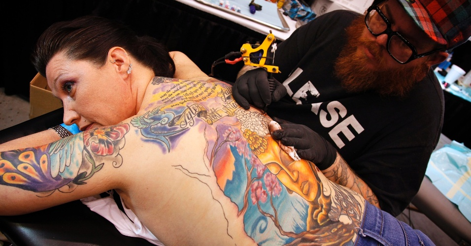 2.mar.2012 - O tatuador Greg French finaliza mais uma tatuagem no corpo de Brittany Keylon, num festival de tatuagem na Virg&#237;nia (EUA). Brittany, que recentemente se divorciou, se curou de um c&#226;ncer e superou a morte do pai, diz que cada tatuagem dela representa sua hist&#243;ria de vida