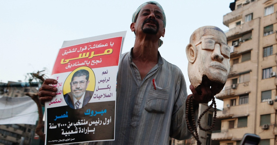 Homem leva &#224; pra&#231;a Tahrir, no Cairo, busto de madeira do primeiro presidente isl&#226;mico do Egito, Mohammed Mursi, que tomou posse neste s&#225;bado (30)