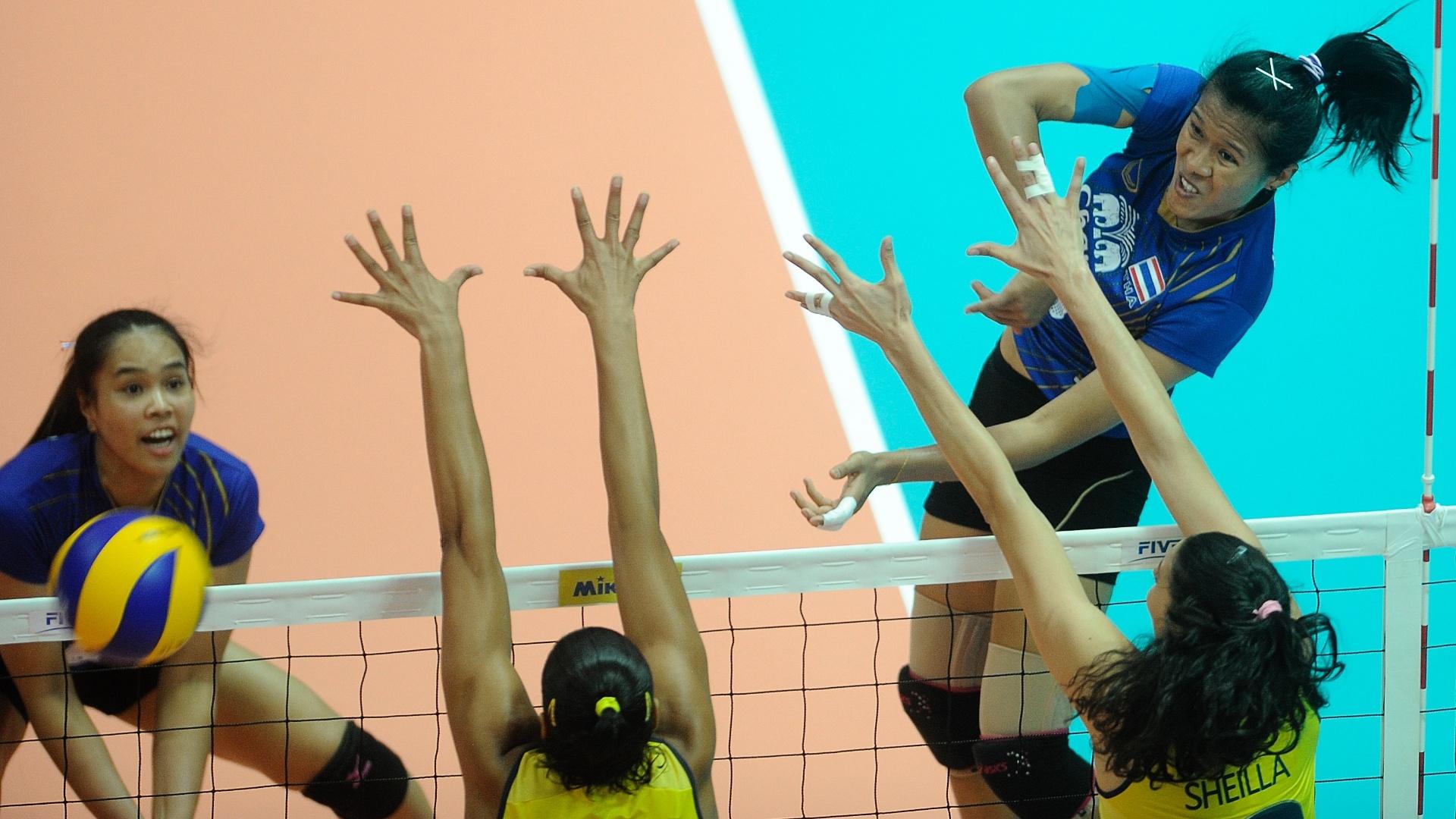 Jogadora tailandesa tenta superar o bloqueio brasileiro