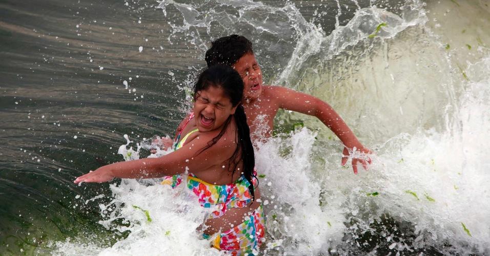 30.jun.2012 - Garoto brinca no mar na praia de Coney Island, perto de Nova York