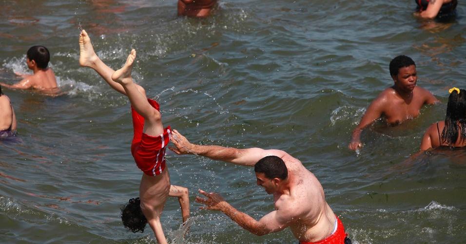 30.jun.2012 - Pessoas brinca no mar na praia de Coney Island, perto de Nova York