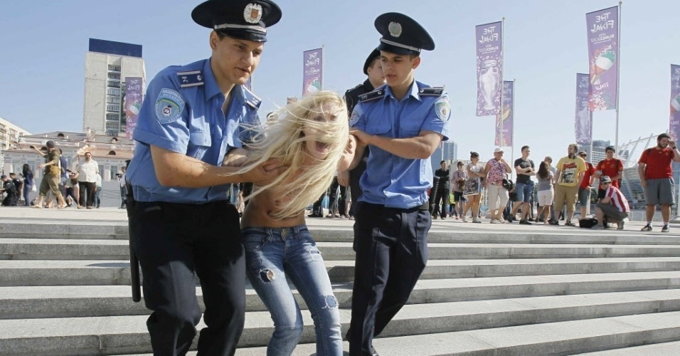 Ativista do Femen  detida pelos policiais aps protesto realizado em frente ao Estdio Olmpico de Kiev contra a presena do presidente da Bielorrssia Alexander Lukashenko