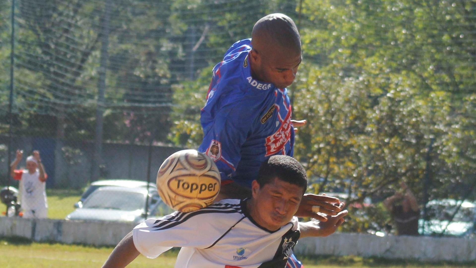 Jogador do Adega (azul) faz a carga em cima do volante do Santos (branco)