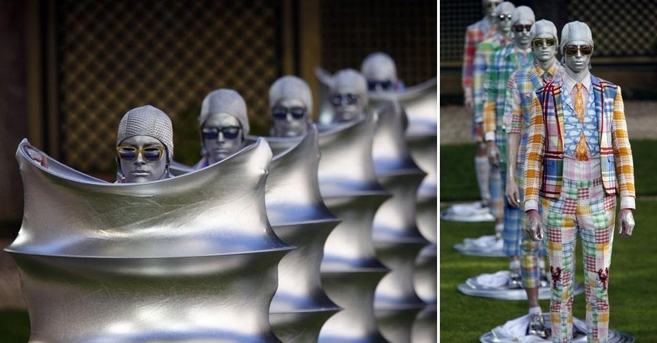 Modelos iniciam desfile dentro de tubos prateados no lançamento da coleção do estilista Thom Browne. Sob os canos metalizados, peças sobrepostas misturam inúmeras cores e estampas