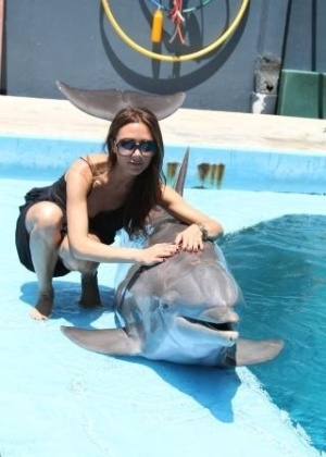 """Victoria Beckham publicou em seu perfil no Twitter uma foto em que aparece com um golfinho em um parque aquático nos EUA. """"Dia muito especial com as crianças, nadando com os golfinhos. Eles são tão lindos"""", escreveu (1/7/12)"""
