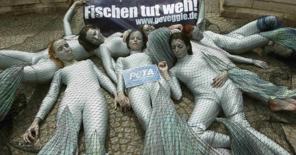 "2.jul.2012 - Ativistas da ONG Peta posam para fotos vestidas como peixe, durante protesto contra o uso de redes de pesca nos oceanos. O cartaz diz ""pescar machuca"""