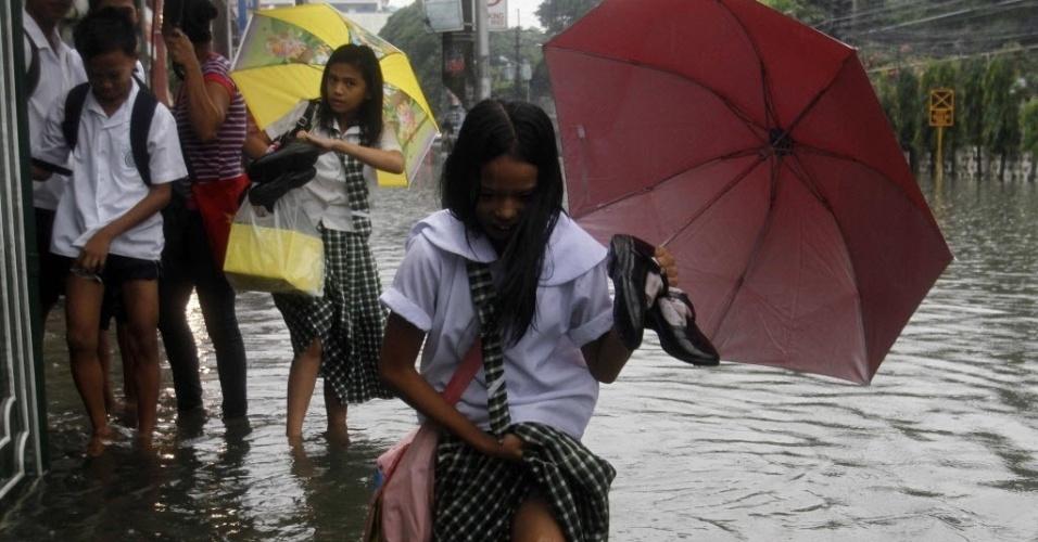 2.jul.2012 - Estudantes caminham em rua com água até os joelhos em rua de Manila, nas Filipinas, após fortes chuvas. O temporal, que inundou estradas da região, fez com que as escolas suspendessem as aulas