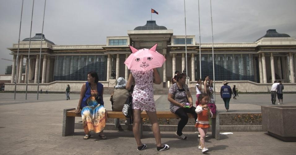 2.jul.2012 - Mulher usa sombrinha com estampa de gato em frente ao prédio do Parlamento, em praça de Ulan Bator, capital da Mongólia