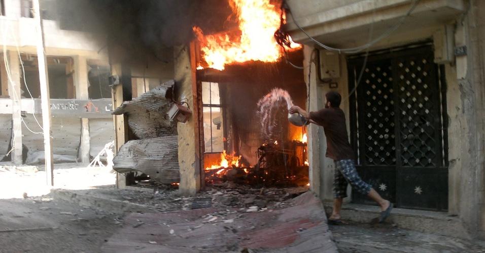 2.jun.2012 - Imagem divulgada pela Rede de Notícias Shaam mostra homem jogando água em sua loja após a mesma ser incendiada em Homs, na Síria