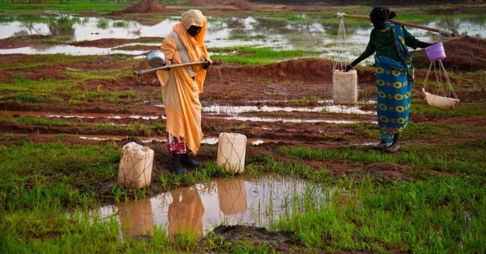 Mulheres recolhem águam em poça de campo para refugiados inundado no Sudão do Sul