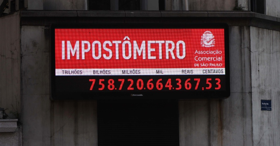 O impost&#244;metro atingiu nesta segunda-feira (2) a marca de R$ 758 bilh&#245;es de impostos federais, estaduais e municipais arrecadados pelos brasileiros. O painel fica localizado na rua Boa Vista, no centro da cidade de S&#227;o Paulo