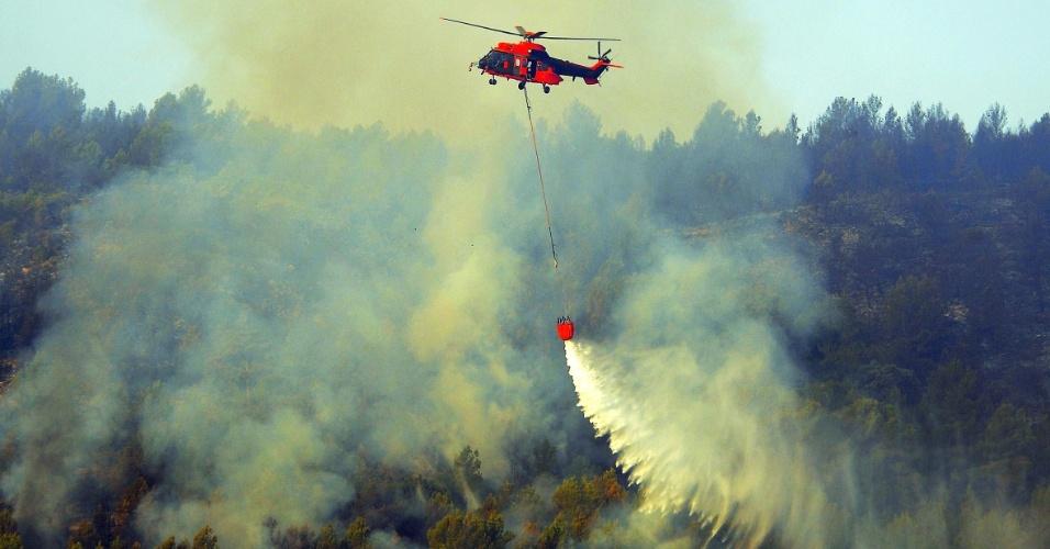 Um helicóptero tenta conter o fogo de um incêndio que tem se espalhado pelas colinas em Altura, perto de Castellon, na Espanha, nesta segunda-feira (2)