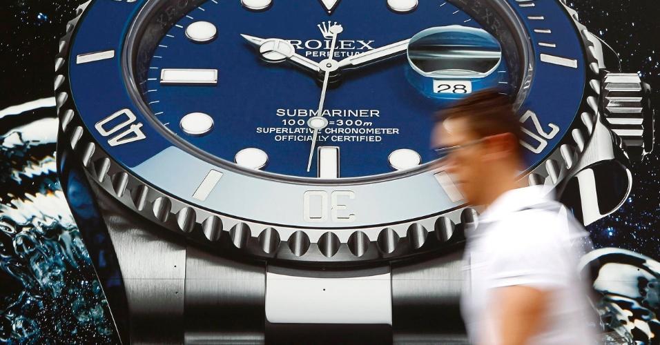 04.jul.2012 - Homem passa por cartaz publicitário da fabricante suíça de relógios Rolex, em Zurique, na Suiça