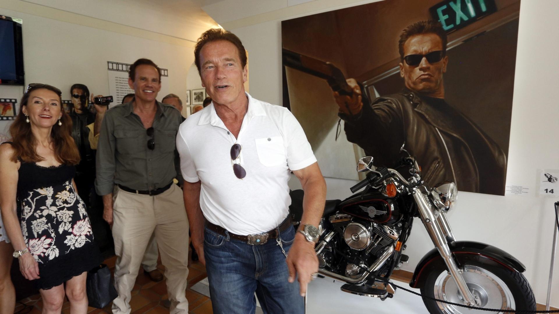 O ator Arnold Schwarzenneger visita museu na Áustria, sua cidade natal, em sua homenagem. Atrás do ator, pôster e moto usada em