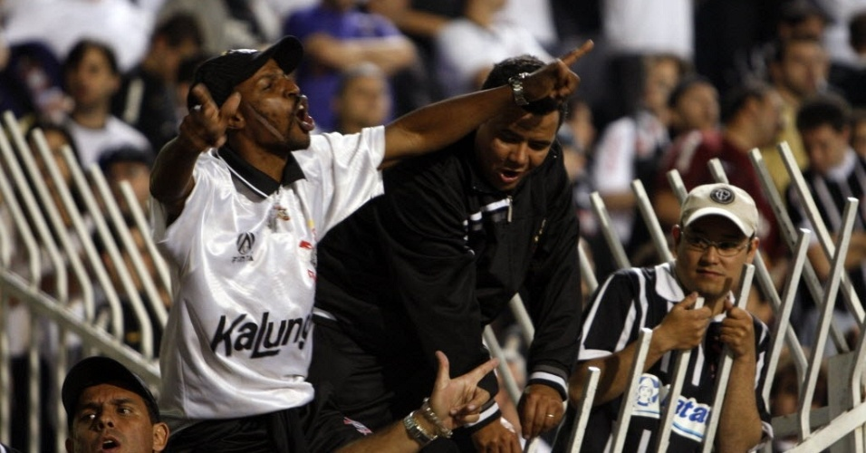 Torcedores do Corinthians sobem em parte do alambrado do estádio do Pacaembu