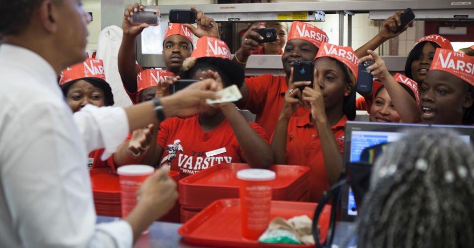 26.jun. 2012 ? Funcionários tiram fotos enquanto o presidente Barack Obama tenta fazer um pedido em restaurante de Atlanta, durante uma parada em um evento de campanha