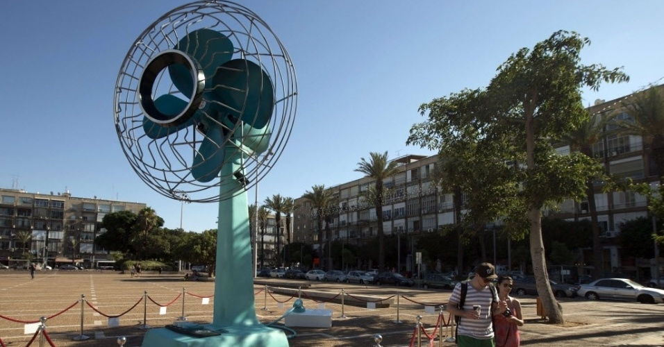 5.jul.2012 - Casal caminha pr&#243;ximo a ventilador gigante instalado na pra&#231;a Rabin, em Tel Aviv, Israel, nesta quinta-feira (5). O ventilador, que tem seis metros de altura, &#233; obra da artista Tal Tenne Czaczkes e &#233; acionado por dois minutos a cada meia hora