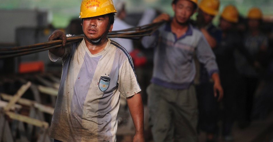 5.jul.2012 - Trabalhadores carregam barras de ferro em Hefei, na China. Eles trabalham na constru&#231;&#227;o de um viaduto para trens-bala depois que o Ministro de Ferrovias do pa&#237;s liberou US$ 24 milh&#245;es (R$ 48 milh&#245;es) para a expans&#227;o da linha ferrovi&#225;ria chinesa