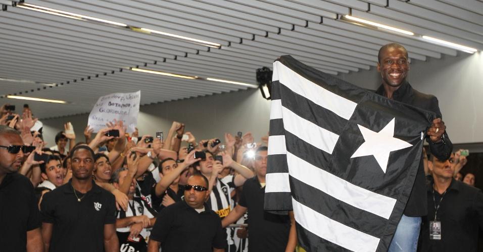 Sorridente, Seedorf segura bandeira do Botafogo na chegada ao Brasil