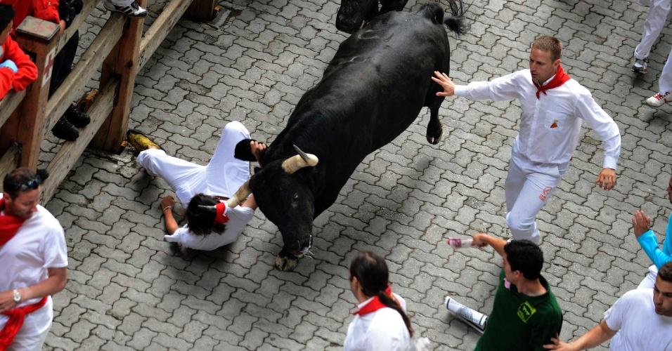 7.jul.2012 - Corredor é arrastado por touro pela camisa durante corrida de touros do Festival San Fermin, em Pamplona, na Espanha