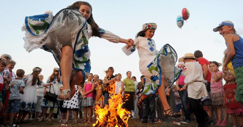 7.jul.2012 - Mulheres usam vestidos tradicionais para pular uma fogueira durante a Noite de Ivan Kupala, um tradicional feriado eslavo, em Belarus