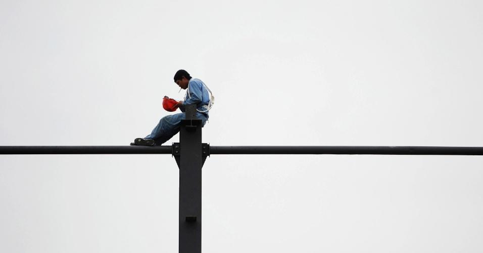 7.jul.2012 -m Operário fuma em estrutura de aço de construção em Hefei, na China