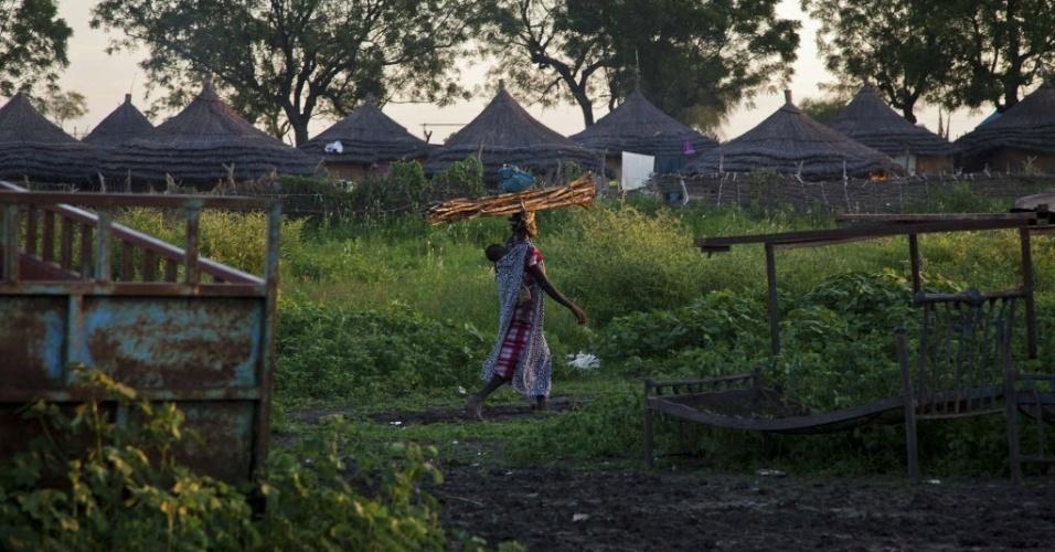 9.jul.2012 - Mulher carrega filho nas costas e pedaços de madeira na cabeça na cidade de Pibor, no Sudão do Sul