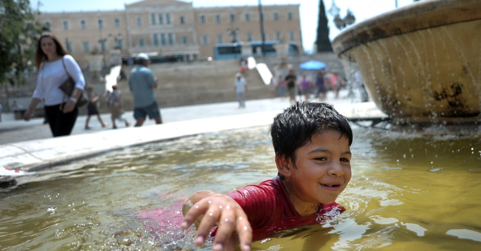 10.jul.2012 - Criança nada em uma fonte no centro de Atenas durante uma onda de calor que atinge a Grécia. As temperaturas em muitas cidades do país chegaram a 40ºC, de acordo com a previsão local