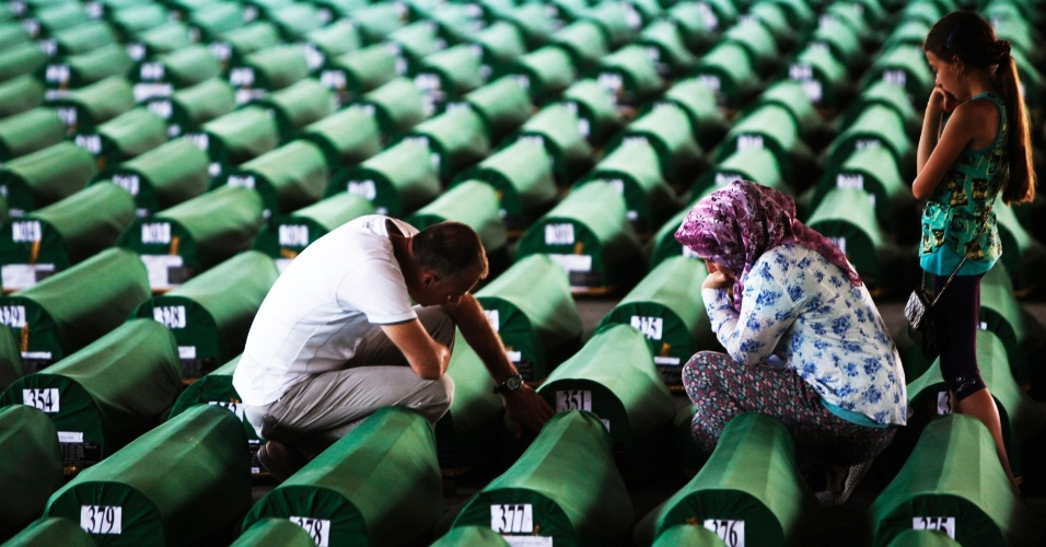 10.jul.2012 - Família da Bósnia vela os restos de um parente antes de um enterro em massa no Memorial de Potocari, próximo da cidade de Srebrenica, nesta terça-feira (10). Corpos de 520 vítimas do massacre de Srebrenica, em que 8.000 muçulmanos foram executados sumariamente em 1995, foram identificados recentemente e serão enterrados na quarta (11)