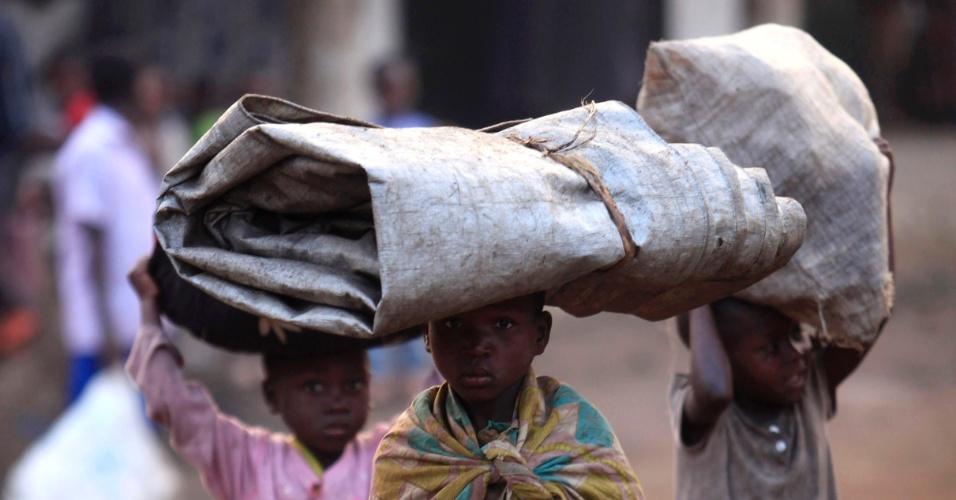 10.jul.2012 - Famílias congolesas atravessam a fronteira de Uganda de volta para a República Democrática do Congo, na região de Bunagana, nesta terça-feira (10). Elas haviam deixado a cidade depois de embates violentos entre rebeldes congoleses e tropas do governo que chegaram a matar um oficial das tropas de paz das Nações Unidas
