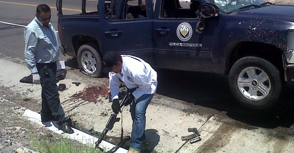 10.jul.2012 - Imagem cedida nesta terça (10) mostra investigadores examinando viaturas que caíram numa emboscada na cidade de Los Mochis, estado de Sinaloa, no México, na segunda-feira (9). Mais de 20 pessoas morreram nos últimos dias em três estados do México, em incidentes violentos envolvendo a polícia e grupos criminais