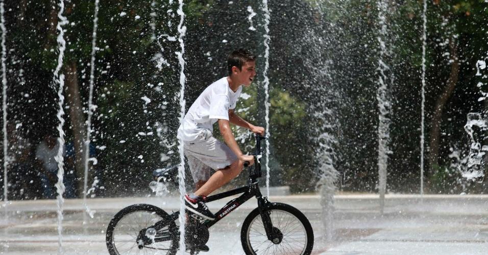 10.jul.2012 - Menino anda de bicicleta em meio a jatos de água de uma praça central de Atenas, na Grécia. As temperaturas em muitas cidades do país chegaram a 40ºC, de acordo com a previsão local