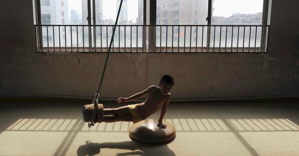10.jul.2012 - Pequeno ginasta chinês pratica movimentos com os pés dentro de um balde em Jiaxing, nesta terça-feira (10)