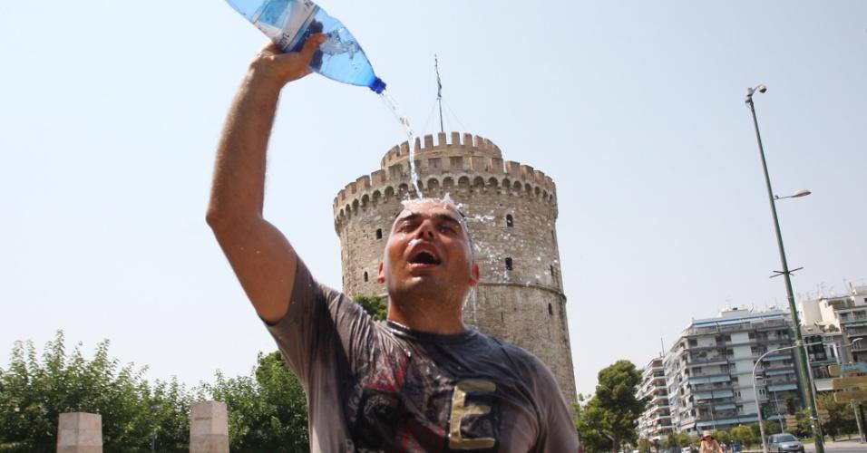 10.jul.2012 - Turista se refresca com uma garrafa de água na cidade de Salónica, na Grécia, durante a onda de calor que atinge o país