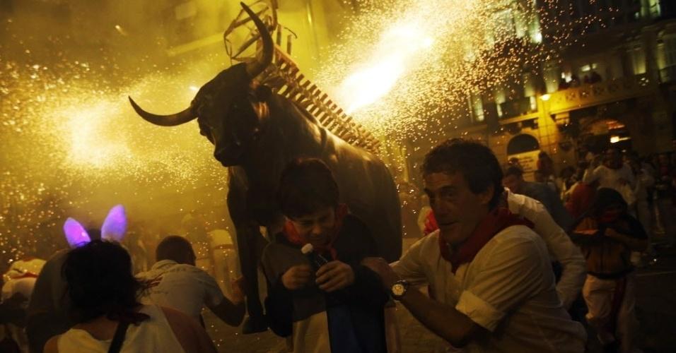 10.jul.2012- Foliões tentam fugir e faísca de fogos de artifícios durante celebrações do festival de São Firmino em Pamplona, na Espanha
