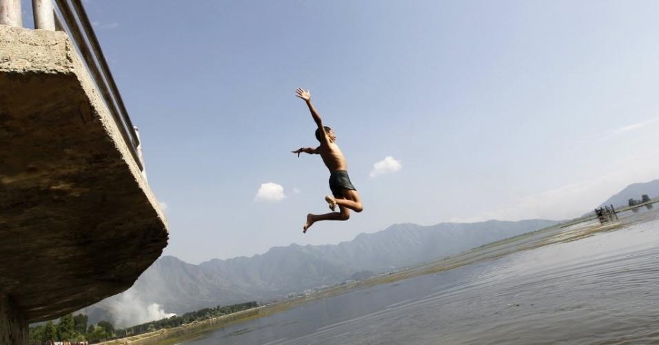 10.jul.2012-Garoto salta em direção a lago em dia quente na região de Srinagar, na Caxemira
