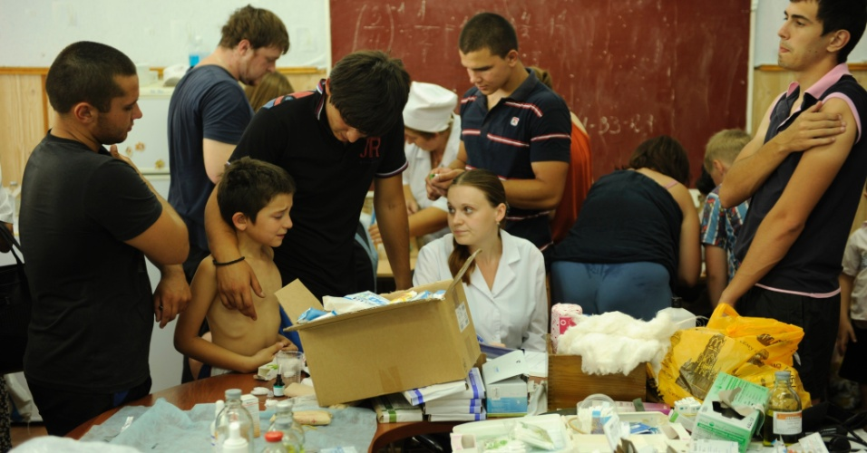 11.jul.2012 - Moradores de Krimsk, na R&#250;ssia, recebem ajuda m&#233;dica tr&#234;s dias ap&#243;s as fortes chuvas que atingiram a regi&#227;o. A enxurrada matou 171 pessoas e 35 mil ficaram desabrigadas ou desalojadas
