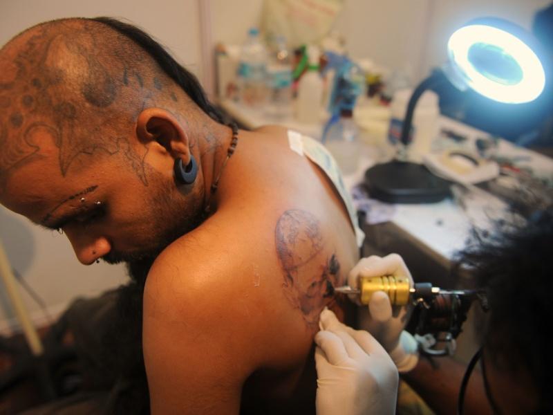 15.jun.2012 - Homem faz tatuagem durante convenção de tatuagem em Mumbai (Índia0