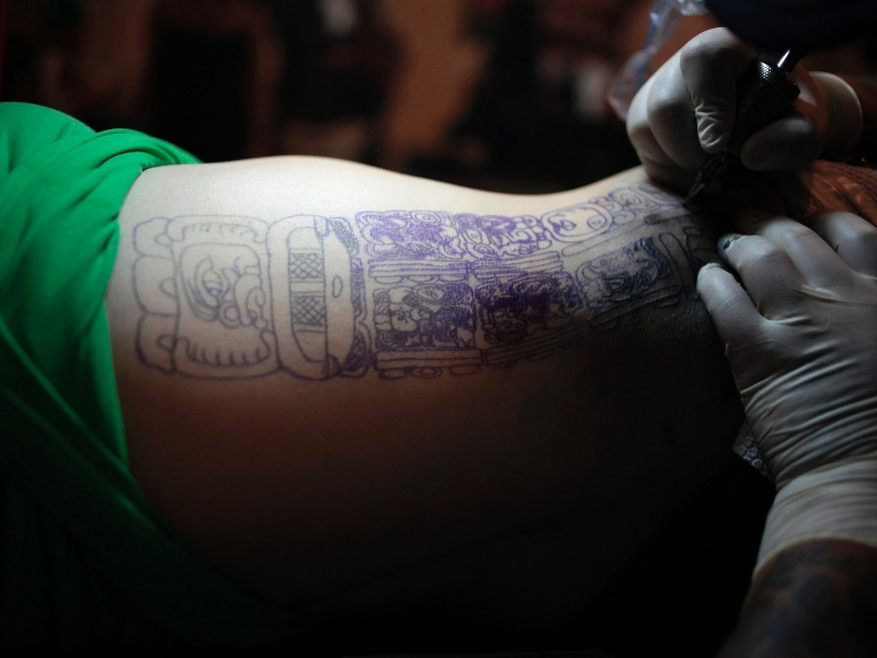 19.mai.2012 - Mulher faz tatuagem durante convenção na Guatemala