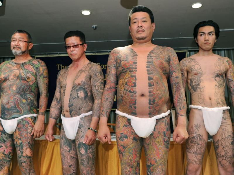 22.mai.2012 - Homens mostram corpos cobertos de tatuagens feitas pelo tatuador japonês Horiyoshii, em Tóquio (Japão)
